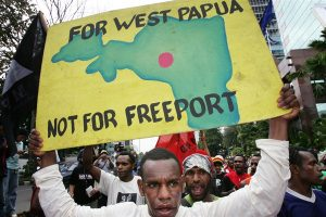 A Papuan protester with a poster of a map of Papua province during a demonstration outside the office of Freeport-McMoRan's Indonesian subsidiary, Jakarta, March 1, 2006, AP photo by Dita Alangkara.